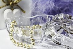 A Still Life of a heart shape glass trinket jar with pearls.  Also a wooden heart and feather boa in the background
