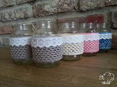 glass jar covered with a crochet cozy, decorated with border lace. The cover is made with cotton yarn. it can be used as small flower vase, pencil holder,