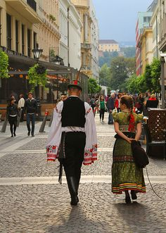 Two Hungarian folk dancers dressed in their traditional costumes, walking through the sunny streets of Budapest Folk Clothing, Sunny Afternoon, Folk Dance, Folk Costume, My Heritage, Walk On, Budapest, Sunnies, Embroidery