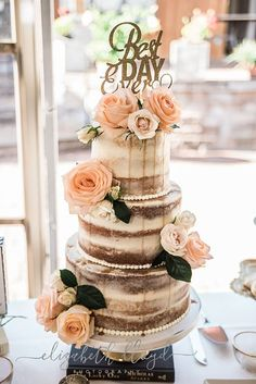 Semi naked wedding cake with drip and decorated with roses.
