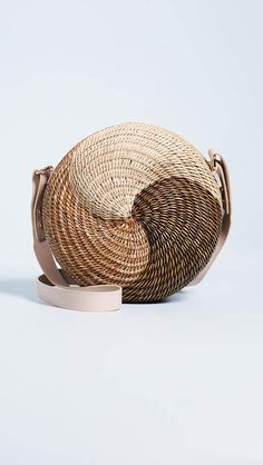 Lucy Folk takes a classic summer style to entirely new heights with this sophisticated straw bag. The circular silhouette is finished with a twisted motif for a polished look that can walk right off the beach. Unique Purses, Unique Bags, Postman Bag, Wooden Bag, Straw Handbags, Round Bag, Basket Bag, Fashion Bags, Fashion Handbags