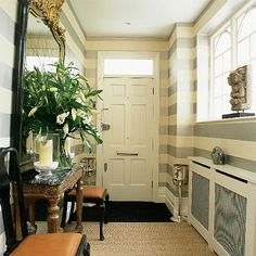 love the horizontal stripes, gold mirror, and entry way table