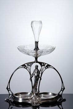 WMF ART NOUVEAU CENTREPIECE In silvered metal, relieved and cast decoration, female figure with a tray, plant motifs and flowers. Cup and flower stand in lapidated crystal. Marked. Germany, c. 1900. Signs of wear, cup with defects (broken and glued) and a loss. Dimension: 73x57x34 cm.