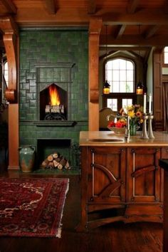 Beautiful kitchen fireplace with green tile (Andie MacDowell's Storybook Tudor in NC)