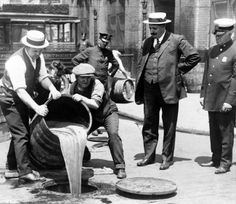 Photo shows New York City Deputy Police Commissioner John A. Leach, right, watching agents pour liquor into sewer following a raid during the height of prohibition. Photo dates to the 1920s.
