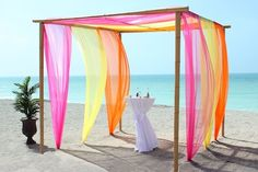 Purple bamboo trellis and sashes for beach wedding