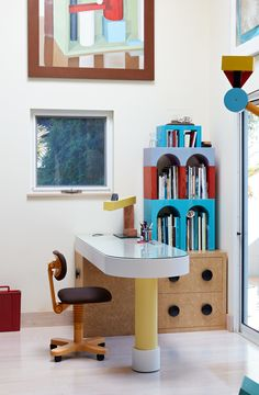 Giotto shelves, a Treetops floor lamp, and an Olivetti chair, all by Sottsass, furnish the home office. Adrian designed the desk, and the painting is by Nathalie Du Pasquier, one of the original Memphis designers.