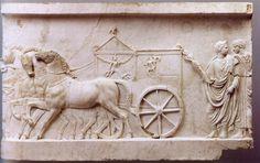 Balra vonuló diadalmenet részlete. Négy ló vontatta kétkerekű díszkocsi (tensa), amelyet elöl a római erények megszemélyesítője (Virtus Romana) húzott. A kocsiszekrényen a hivatalossá tett római őstörténet három fordulópontját ábrázolták. A kocsi mögött babérágat tartó togás férfi, mögötte szintén togába öltözött, sima arcú ifjú.  Az ún. Actium-reliefek egyik darabja.  (http://classics.mfab.hu/hyperion/targy.php?id=419)
