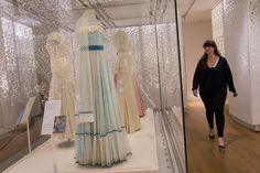 """An employee walks past a display of dresses, including one by designer Catherine Walker (C), and worn by Britain's Diana, Princess of Wales at the Christie's gala in New York in 1997, during a press preview of the forthcoming exhibition entitled """"Diana: Her Fashion Story"""", at Kensington Palace in London on February 22, 2017..Glittering gowns, elegant suits and bold mini-dresses worn by the late Princess Diana will go on show from Friday on the 20th anniversary of her death in a unique…"""