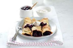 Low-Carbohydrate Paleo Crepes made with 4 ingredients --coconut flour, eggs, coconut oil, and water. Serve with blueberry filling and coconut whipped cream.