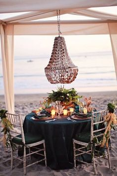 Heaven-romantic beach date setting with chandelier and canopy with candles