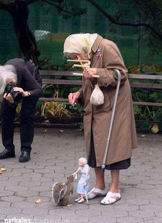 PUPPETEER FEEDING  An elderly woman has received a puppet that she controls so as to feed squirrels at their own level. She frequents Washington Square Park in New York City. There's a man who makes the marionettes and puts on shows. He made this woman in marionette form.