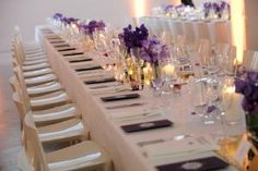 Banquet-style dinner tables were given a sleek, modern look with purple orchids and candles arranged atop mirrored runners.