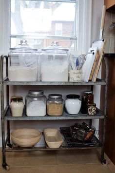 Make kitchen essentials part of the decor. Glass storage jars and wooden boards on a rusted metal cart are an easy way to add to any apartment or rental space
