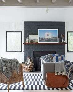 Sonoma farmhouse: Bloom took a living room with shag carpeting, dark-stained plywood and a red-brick fireplace and turned it into an, airy space. Dark gray paint transforms the fireplace; black windows lend a modern touch. The midcentury American pieces — sofa and console — have clean lines, and the vintage rug and textiles bring in texture and warmth. Photo: John Merkl