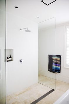 White mosaic wall tiles line the ensuite bathroom while travertine floor tiles provide contrast and warmth to this renovated terrace home. White Mosaic Tiles, White Wall Tiles, White Bathroom Tiles, Mosaic Bathroom, Bathroom Floor Tiles, Bathroom Wall, Tile Floor, Mosaic Wall, White Bathrooms