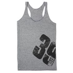 """Own it, earn it, in this lightweight premium heather tank. The racerback style gives you the freedom to move, and the relaxed fit makes layering easy. This tank features """"39 miles"""" on the front, and """"Earn Your 39"""" on the back. Net proceeds go to the Avon Breast Cancer Crusade."""