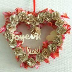 Couronne de Noël réalisée avec des fleurs en papier (partitions de musique) et nœuds en tissu coloré