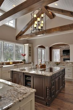 Ooo, Aahh Kitchen!  Love the beams, tons of counter space, mega island, open & airy feel with major windows, a cool chandelier, repurposed looking floors & must have (another) farm house sink.