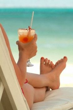 Vacation, sun and sand. A comfy chair and a cool drink at the beach.