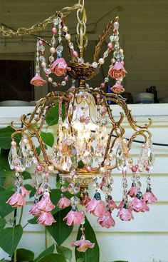 This is SOLD! PLease DO NOt PUrchASE...   A stunning antique brass basket chandelier covered in antique pink porcelain roses.  The top prism holder is draped in strands of crystal beads and pearls in pink, light rose, and dark rose, and porcelain roses. The center of the chandelier holds a capodimonte cup which houses the standard light socket. It is surrounded with Austrian crystal rose prisms and large clear prisms, with tiny pink teardrops. The ten arms are draped in the crystal and pearl…