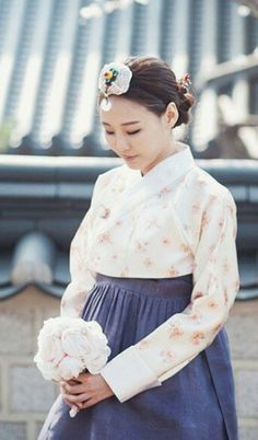 This bride wears a hanbok—Korea's traditional two piece formal dress—with modern touches, like a floral-printed top.