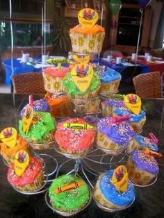 I created this cupcake stand display for my daughter's 6th birthday.  I frosted the cupcakes with vibrant, primary colors and topped with crayons and crayon box decorations.  The cupcakes were then placed on a metal cupcake stand.