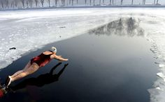A winter swimmer dives into the freezing water of Beijing Lake in Shenyang, China