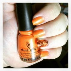 Orange nail art with glitter accent nail