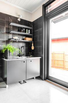 Kannustalo Pohjanmaa. Keittiön seinässä Via Emilia nero 20x20 cm ja lattiassa Res-Cover beton kiiltävä K60x60. #pukkilalaatat #pukkila
