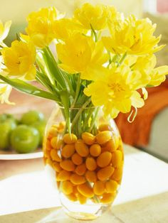 Add colors below the vase line to complement the single-tone flowers above. Drop handfuls of kumquats, cherries, or cranberries into the vase