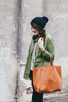 Cable hat, olive green jacket, leather tote.