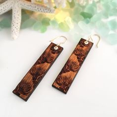 THE CREATION  ʻOhiʻa Lehua Carved design in Hawaiian Koa Wood from the Big Island of Hawaii. Measures approximately: 5.5 cm or 2.13 inches Metal: 14k gold filled  Just a little bit of Manaʻo (knowledge): The ʻOhiʻa Lehua is endemic and vital to Hawaiʻi's ecosystem. It was known to be used for building heiau, canoes and temple posts. The leaves, Liko and Lehua are popular for lei but were also used for dying kapa, making offerings and medicinally to cure congestion and aid in childbirth....