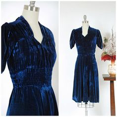 Vintage early 1940s cocktail dress is a dream in lovely royal blue velvet. This velvet is incredibly soft with a lot of luster, but it tests as a blend and Im not sure of the content. Perhaps cotton and rayon? Shirring at either shoulder and again to the side of the collar creates a lovely drape along the bodice. This effect is emphasized further by the four inch, shirred and elasticized waist. The sleeves are a clamshell style. The skirt is incredibly full, and so it drapes marvelously…
