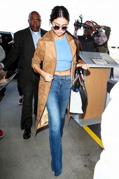 Selena Gomez wears a crop top, jeans, trench coat, and round sunglasses