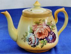 From the Collection of Orbost & District Historical Society Johnson Brothers round china teapot with yellow/orange background colour. Blue,pink and purple rose on front and back.  Size: H-120mm D-350mm