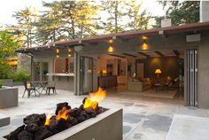 Bi-fold doors open up to poured concrete patio. Oversized lava rock in the fire pit. Exterior wall covered with smooth troweled plaster in grey.