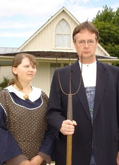"""""""The American Gothic house, as painted by Grant Wood, in the background. The nearby visitor center have various clothes, a pitchfork, glasses, that visitors can dress up in and have their photograph taken, in front of the house, parodying the original painting. The picture shows John Kirriemuir and Becky Yoose in such clothing."""""""