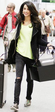 Street Style September 25, 2014 As she arrived at the airport in Milan to kick off her wedding weekend, Mrs. Clooney showed off her put-together jet-set style in a neon T-shirt, black moto jacket, distressed skinny jeans, and sleek metallic oxford shoes.