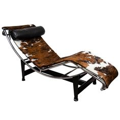This is a Mid Century Le Corbusier lounge chair. The chair sits on a stand so that it can recline. The seat is cowhide with a leather headrest.