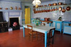 Claude Monet's kitchen. White tile walls, terracotta floor, yellow and turquoise accent, blue and white tile, copper pots