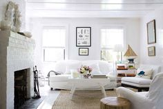 Keep It Simple: Use high-gloss white paint on a ceiling to reflect natural light. Dress-up paired down furnishing like this vintage sofa, covered in easy-to-wash white canvas and a jute rug that's both affordable and fuss-free. An antique sea coral print hangs between the windows adds some crisp color for good measure.