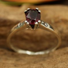 Red spinal oval faceted ring in prongs setting and diamond side set with sterling silver band