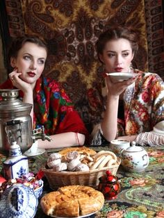 Two girls in Russian Pavlovsky Posad shawls at the tea-table.