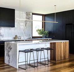 Love the asymmetry of the island with wood accent and waterfall edges.