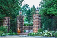 Brick pillars adorned with wrought-iron fencing create a stately side entry.