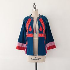 """VINTAGE   Colorful Cotton Tassel Jacket Vintage 1970s jacket just waiting to become your signature piece, but a warning, its only for the bold!   FEATURES:  • Medium weight 100% cotton  • Embroidery detail throughout  • Collarless with double ties at the neck  • Hot pink tassels throughout  • 3/4 sleeves   MEASUREMENTS: Bust - 38"""" Waist - 40""""  Length - 25"""" Measurements are approximate, taken flat and doubled.  ✅ Very good vintage condition ⛔️ NO SWAPS Vintage Jackets & Coats"""