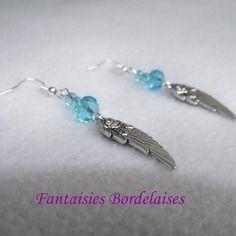 Boucles d'oreilles bleu turquoise avec ailes d'ange argentées  Paire de boucles d'oreilles tendances composées de 2 petites et une grande perles à facettes en cristal bleu turquoise et d'ailes d'ange ornées d'une fleur en métal argenté.  Support en métal argenté sans nickel.  #boucles #ailes #ange