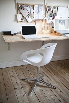 Home office | Raw wooden floor, bulletin boards + modern white swivel chair