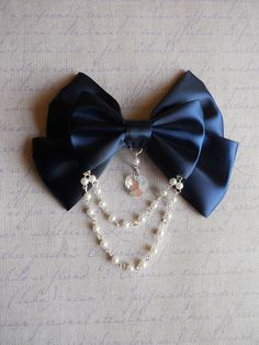 Lolita inspired bow ! : )    Romantic navy bow with a glass heart and bead in the middle. With white pearl beads. You have the option of Brooch or